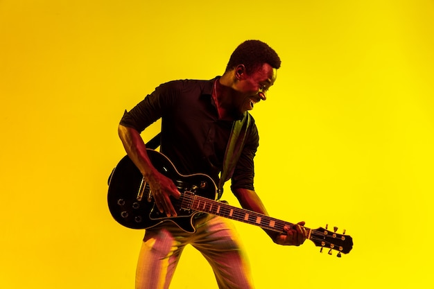 Junger afroamerikanischer musiker, der gitarre wie ein rockstar auf gelber wand im neonlicht spielt.