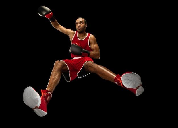 Junger afroamerikanischer professioneller boxer in aktion, bewegung lokalisiert auf schwarzem hintergrund