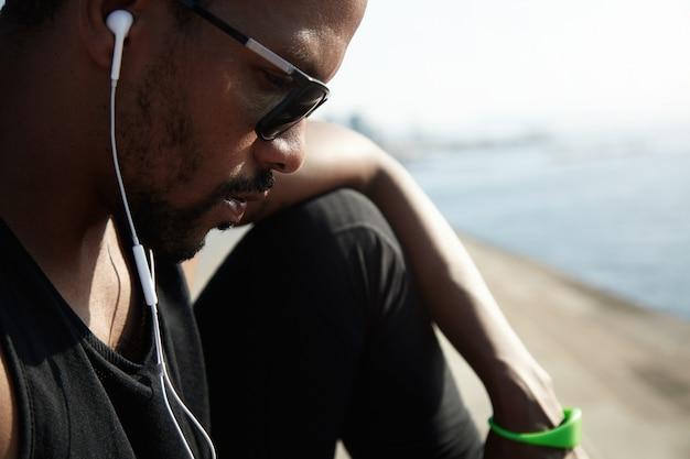 Junger afroamerikanischer rapper in der schwarzen spitze, die neue spuren draußen unter blauem himmel hört. hübscher und ernster mann, der allein am straßenrand sitzt und mit seinen freunden auf seinem digitalen gerät plaudert.
