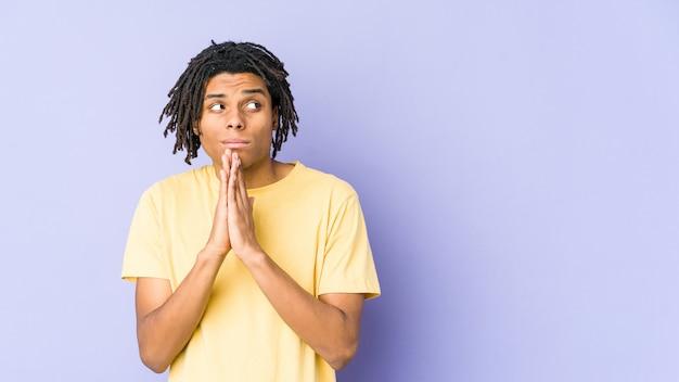 Junger afroamerikanischer rastaman, der betet und hingabe zeigt, religiöse person, die nach göttlicher inspiration sucht.