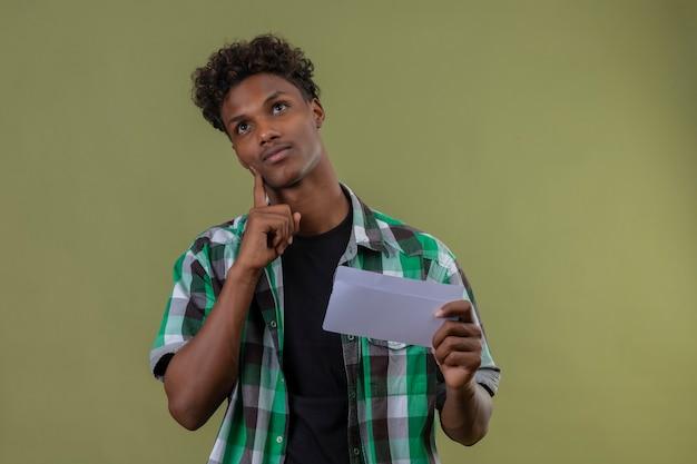 Junger afroamerikanischer reisender mann, der brief hält, der mit finger auf kinn mit nachdenklichem ausdruck denkt, der über grünem hintergrund steht