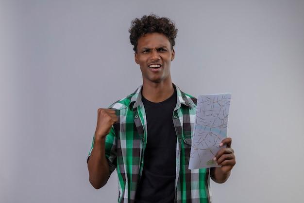 Junger afroamerikanischer reisender mann, der die karte hält, die die faust hebt, verließ und glücklich, die faust zu heben, die seinen erfolg erfreut, der über weißem hintergrund steht