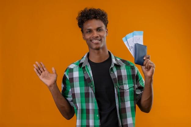 Junger afroamerikanischer reisender mann, der flugscheine hält, die fröhlich positiv und glücklich betrachten kamera, die über orange hintergrund steht