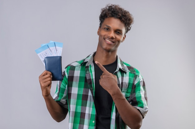 Junger afroamerikanischer reisender mann, der flugtickets hält, die mit finger auf sie zeigen, die fröhlich, positiv und glücklich lächeln