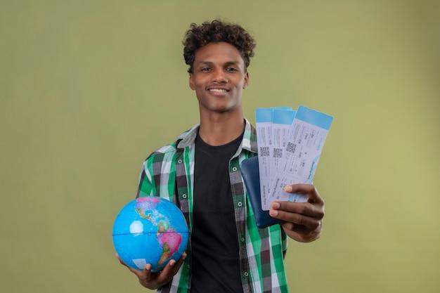 Junger afroamerikanischer reisender mann, der globus hält, der flugtickets zeigt, die fröhlich über grünem hintergrund stehen