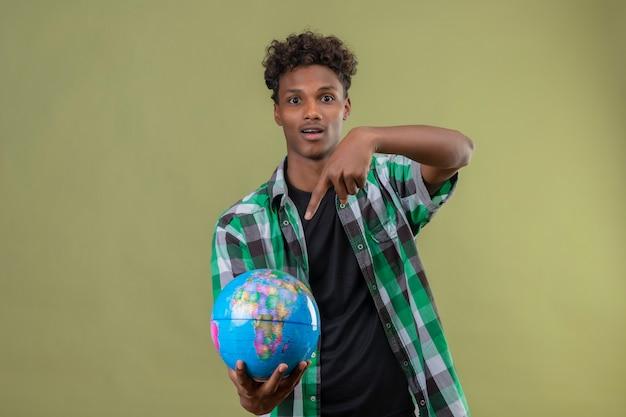 Junger afroamerikanischer reisender mann, der globus hält, der mit dem finger auf ihn schaut, der die kamera verließ