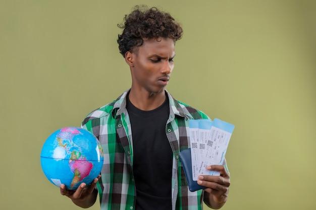 Junger afroamerikanischer reisender mann, der globus und flugtickets hält, die sie mit ernstem ausdruck auf stirnrunzeln betrachten, die über grünem hintergrund stehen