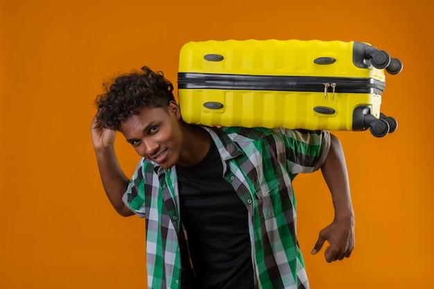 Junger afroamerikanischer reisender mann, der koffer auf seinem rücken hält, der das positive lächeln der kamera betrachtet, das über orange hintergrund steht