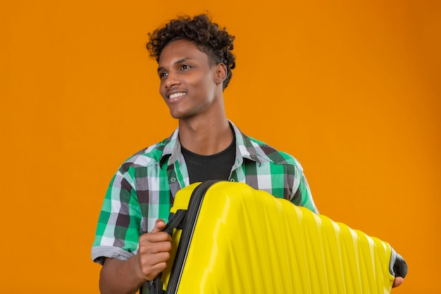 Junger afroamerikanischer reisender mann, der koffer hält, der glücklich und positiv lächelnd beiseite schaut