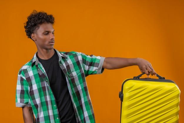 Junger afroamerikanischer reisender mann, der koffer hält, der ihn mit verwirrendem ausdruck auf gesicht betrachtet, das zweifel hat, die über orange hintergrund stehen