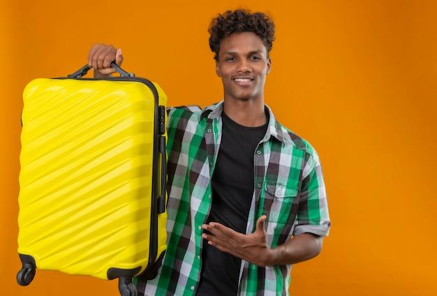 Junger afroamerikanischer reisender mann, der koffer hält, der mit arm seiner hand betrachtet kamera betrachtet, die zuversichtlich, positiv und glücklich lächelt