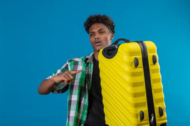 Junger afroamerikanischer reisender mann, der koffer hält, der mit dem finger darauf schaut und beiseite lächelnd zuversichtlich steht über blauem hintergrund