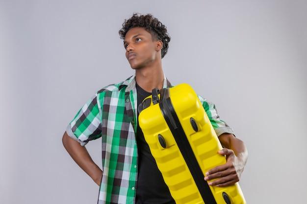 Junger afroamerikanischer reisender mann, der koffer hält, der mit nachdenklichem ausdruck auf gesicht beiseite schaut, denkt