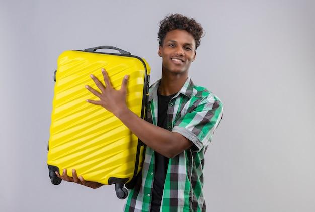 Junger afroamerikanischer reisender mann, der koffer hält kamera betrachtet, die fröhlich positiv und glücklich über weißem hintergrund stehend lächelt