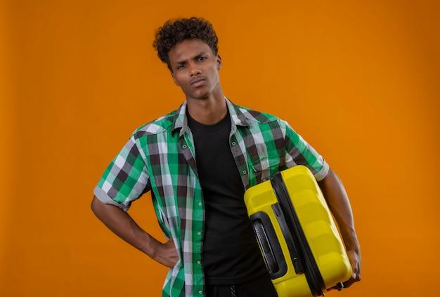 Junger afroamerikanischer reisender mann, der koffer hält kamera betrachtet unzufrieden mit stirnrunzelndem gesicht, das über orange hintergrund steht