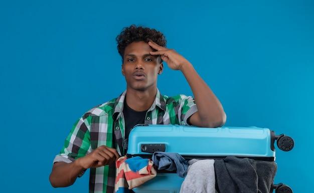 Junger afroamerikanischer reisender mann, der koffer voll von kleidern hält, die gelangweilt und müde suchen