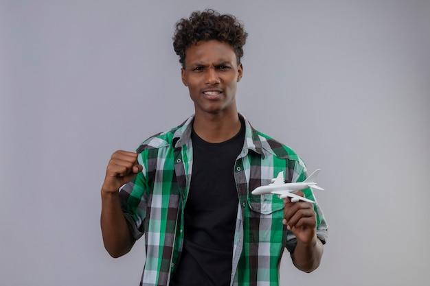 Junger afroamerikanischer reisender mann, der spielzeugflugzeug hält, das faust erhöht und freudiges erhöhen der faust freut sich über seinen erfolg, der über weißem hintergrund steht