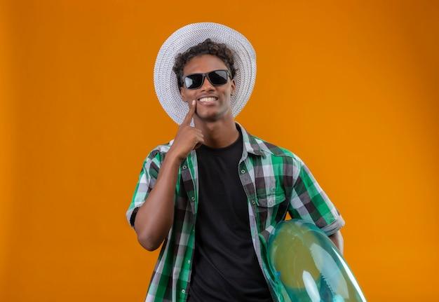 Junger afroamerikanischer reisender mann im sommerhut, der schwarze sonnenbrille hält, die aufblasbaren ring betrachtet kamera mit großem lächeln auf gesicht zeigt, das mit finger auf sein lächeln steht, das über ora steht