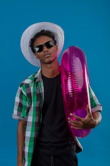 Junger afroamerikanischer reisender mann im sommerhut, der schwarze sonnenbrille hält, die aufblasbaren ring betrachtet kamera mit sicherem ernstem ausdruck auf gesicht steht, das über blauem hintergrund steht