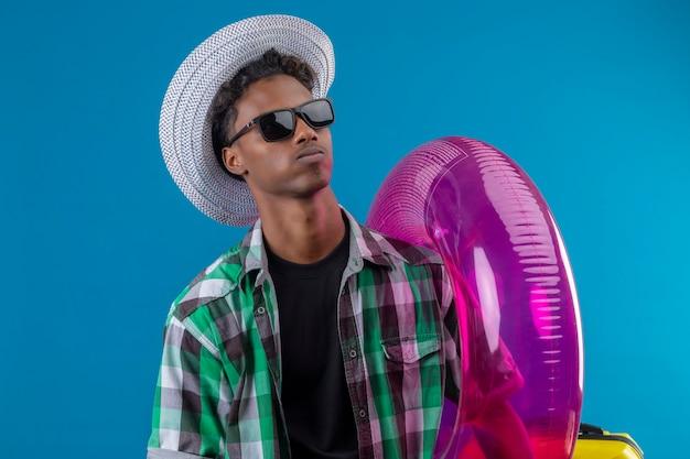 Junger afroamerikanischer reisender mann im sommerhut, der schwarze sonnenbrille hält, die aufblasbaren ring hält, der beiseite mit sicherem ernstem ausdruck auf gesicht steht, das über blauem hintergrund steht