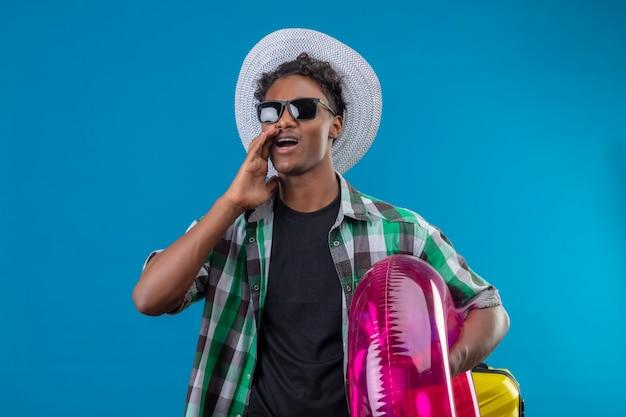 Junger afroamerikanischer reisender mann im sommerhut, der schwarze sonnenbrille hält, die aufblasbaren ring hält, der beiseite schreit oder jemanden ruft, der über blauem hintergrund steht