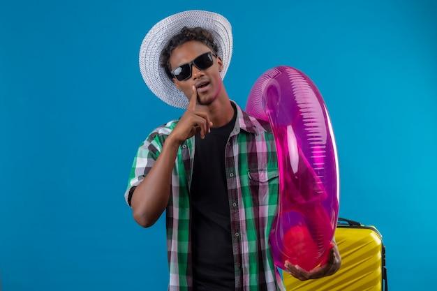 Junger afroamerikanischer reisender mann im sommerhut, der schwarze sonnenbrille hält, die aufblasbaren ring hält, der kamera mit dem selbstbewussten ausdruck lächelt, der über blauem hintergrund steht