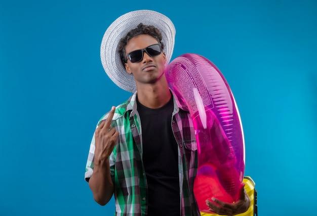 Junger afroamerikanischer reisender mann im sommerhut, der schwarze sonnenbrille hält, die aufblasbaren ring hält, der zuversichtlich zufrieden zeigt, mittelfinger stehend über blauem hintergrund