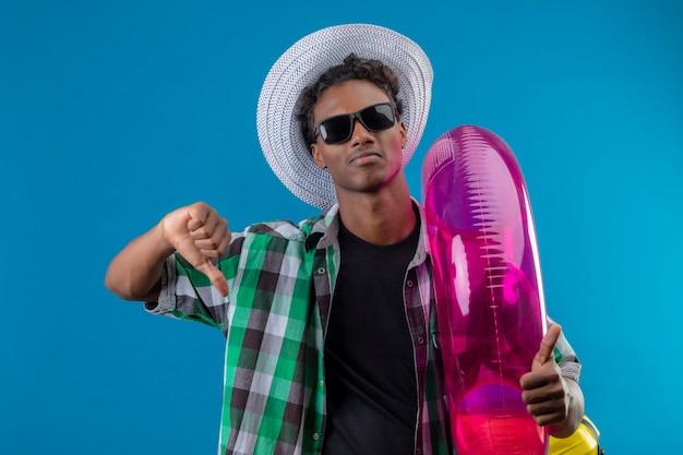 Junger afroamerikanischer reisender mann im sommerhut, der schwarze sonnenbrille hält, die aufblasbaren ring hält unzufrieden zeigt daumen unten stehend über blauem hintergrund