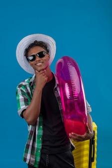Junger afroamerikanischer reisender mann im sommerhut, der schwarze sonnenbrille steht, die mit koffer hält, der aufblasbaren ring hält, der kamera betrachtet, die fröhlich über blauem hintergrund lächelt