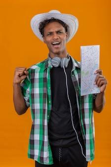 Junger afroamerikanischer reisender mann im sommerhut mit kopfhörern, die karte halten, die faust anhebt, verlassen und glückliche anhebende faust, die seinen erfolg freut, der über orange hintergrund steht