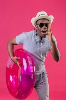 Junger afroamerikanischer reisender mann im sommerhut mit kopfhörern um seinen hals, der schwarze sonnenbrille hält, die aufblasbaren ring hält, der jemanden mit hand nahe mund ov schreit oder ruft
