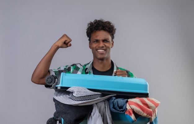 Junger afroamerikanischer reisender mann mit koffer voll von kleidern, die faust glücklich erheben und sich freuen, seinen erfolg zu freuen