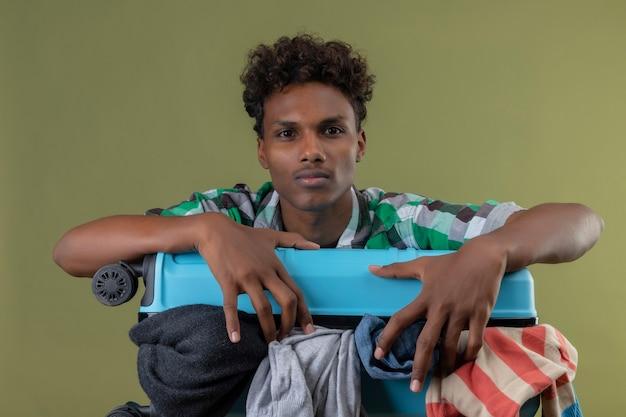 Junger afroamerikanischer reisender mann mit koffer voll von kleidern, die kamera mit ernstem selbstbewusstem ausdruck auf gesicht betrachten