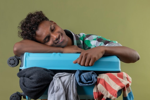Junger afroamerikanischer reisender mann mit koffer voll von kleidern, die müde schlafen auf ihm über grünem hintergrund suchen