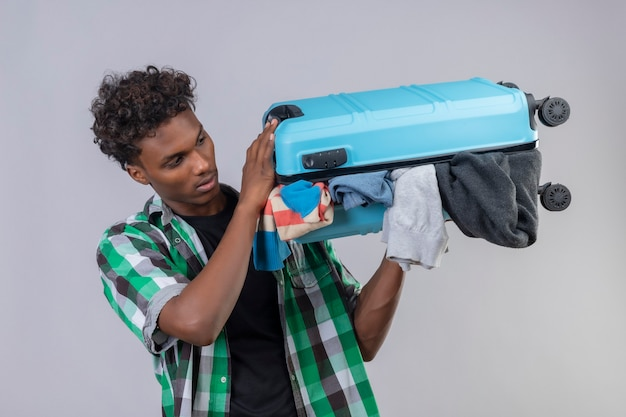 Junger afroamerikanischer reisender mann mit koffer voll von kleidern, die verwirrt schauen