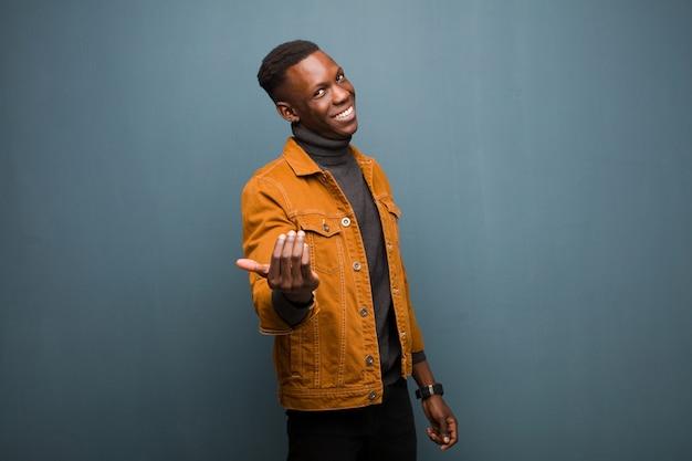 Junger afroamerikanischer schwarzer mann, der glücklich, erfolgreich und zuversichtlich fühlt, sich einer herausforderung stellt und sagt, bringen sie es auf! oder dich gegen die grunge-wand begrüßen