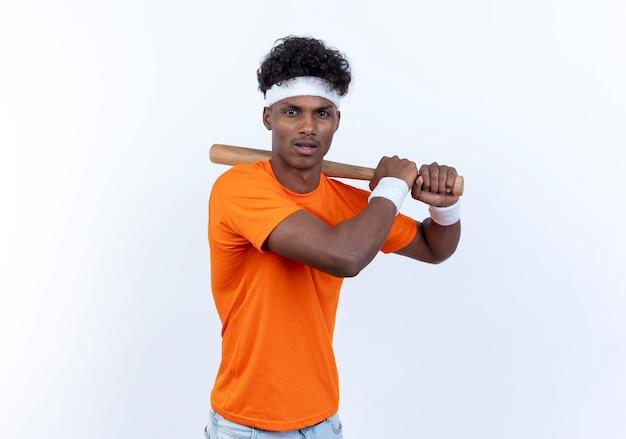 Junger afroamerikanischer sportlicher mann, der stirnband und armband hält fledermaus um schulter hält