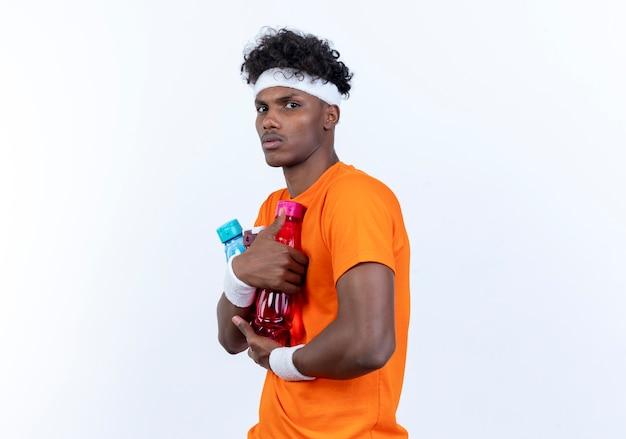 Junger afroamerikanischer sportlicher mann, der stirnband und armband hält wasserflasche hält