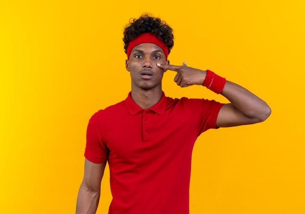 Junger afroamerikanischer sportlicher mann, der stirnband und armband trägt, die finger auf auge lokalisiert auf gelber wand setzen