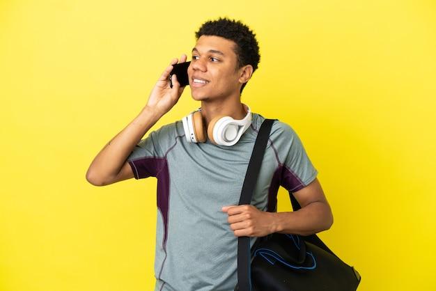 Junger afroamerikanischer sportmann mit sporttasche isoliert auf gelbem hintergrund, der ein gespräch mit dem mobiltelefon führt