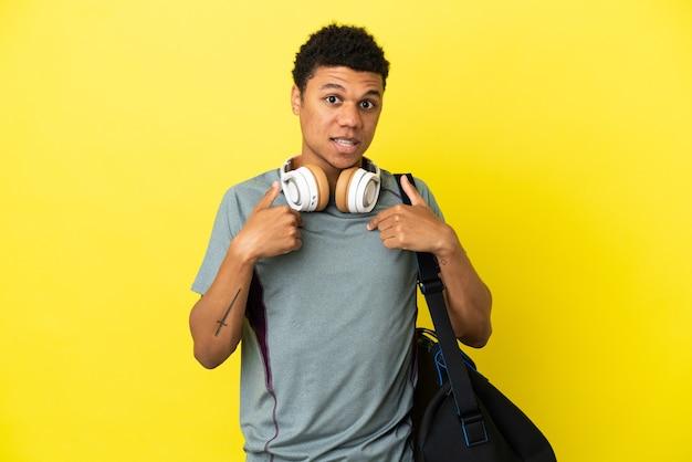 Junger afroamerikanischer sportmann mit sporttasche isoliert auf gelbem hintergrund mit überraschendem gesichtsausdruck