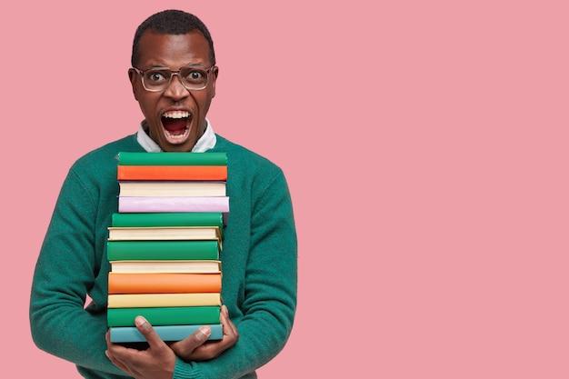 Junger afroamerikanischer student, der stapel bücher hält