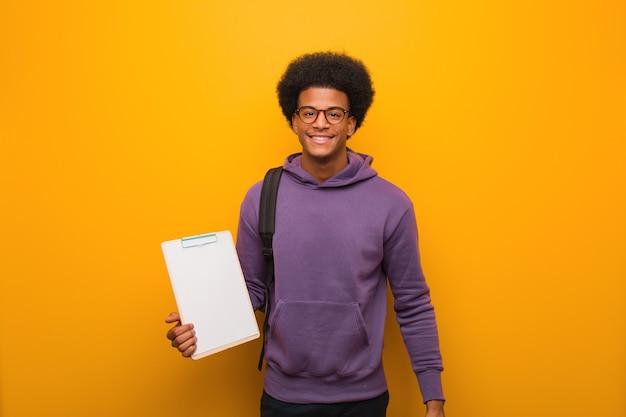 Junger afroamerikanischer studentenmann, der eine zwischenablage mit einem großen lächeln fröhlich hält