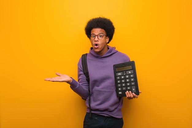 Junger afroamerikanischer studentenmann, der einen taschenrechner hält, der etwas auf handfläche hält