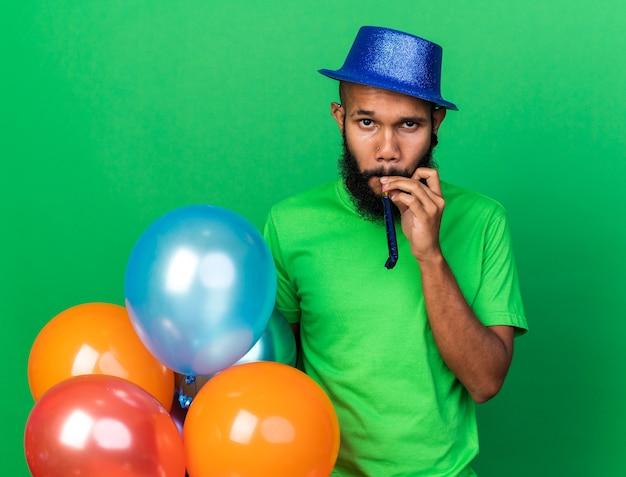 Junger afroamerikanischer typ mit partyhut bläst partypfeife isoliert auf grüner wand