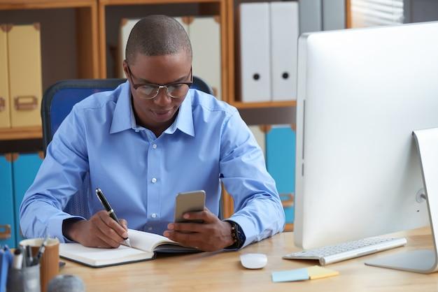Junger afroamerikanischer unternehmer, der den tag plant