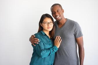 Junger afroer-amerikanisch Mann, der seine asiatische Freundin mit Gläsern umarmt.