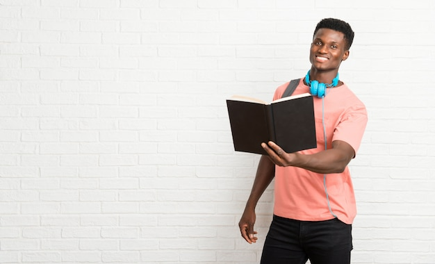 Junger afroer-amerikanisch mannstudent, der ein buch liest