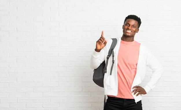 Junger afroer-amerikanisch mannstudent, der einen finger im zeichen des besten zeigt und anhebt