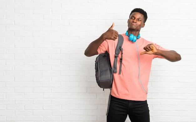 Junger afroer-amerikanisch mannstudent, der gut-schlechtes zeichen macht. unentschiedene person zwischen ja oder nein